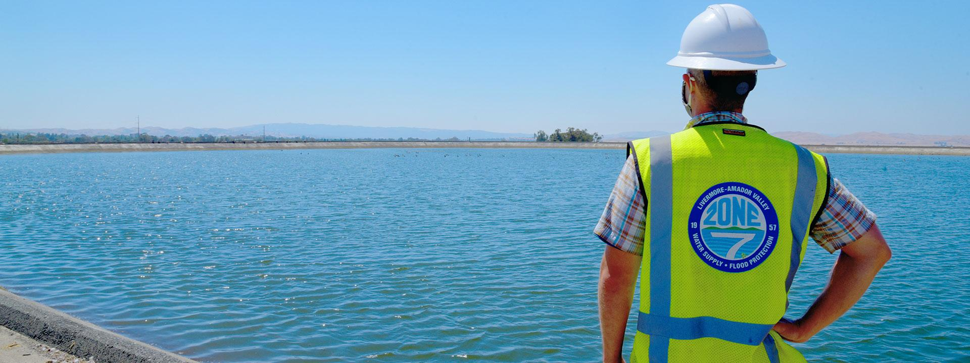 Zone 7 Engineer wearing a white hard hat and a yellow hazard vest looking out to a body of water