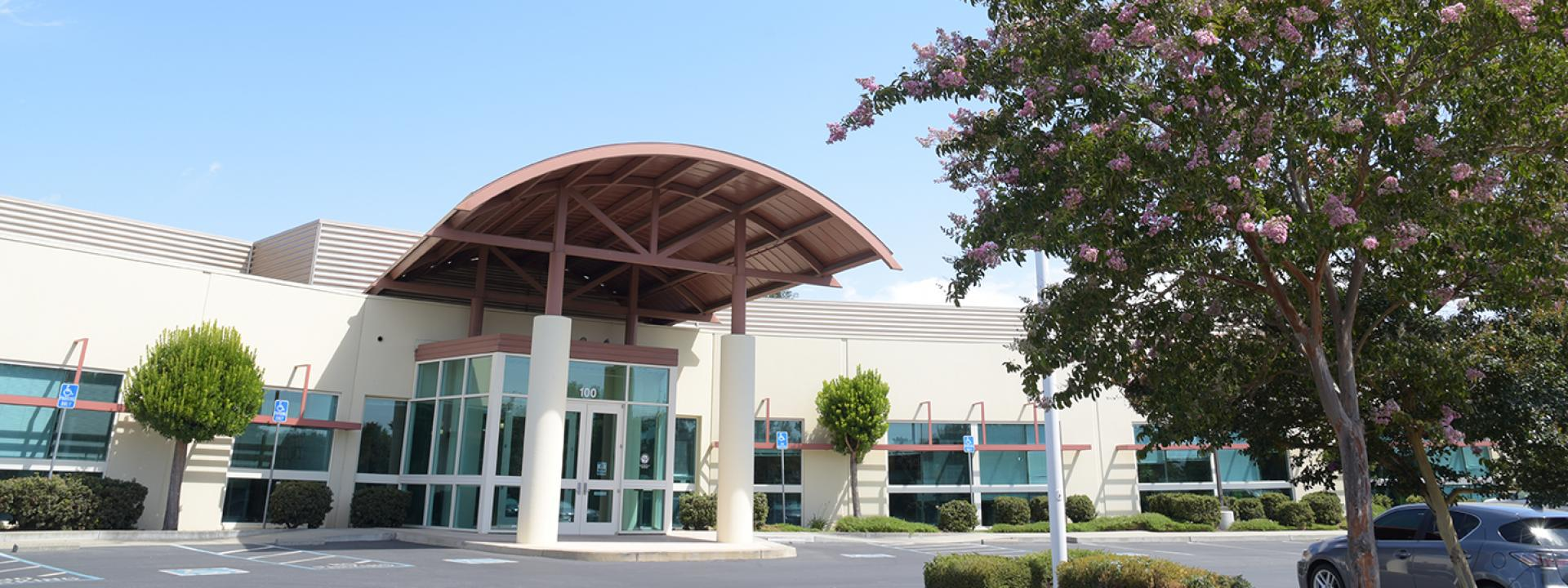The front of Zone 7's administrative building with blue sky, cloud, and trees