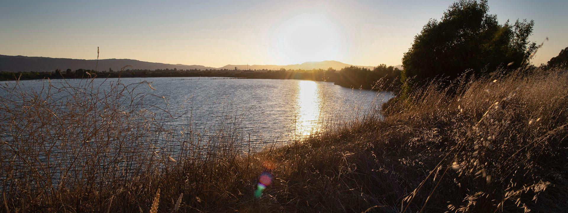 A blue lake surrounded by greenery and trees with a sunset reflected in the lake