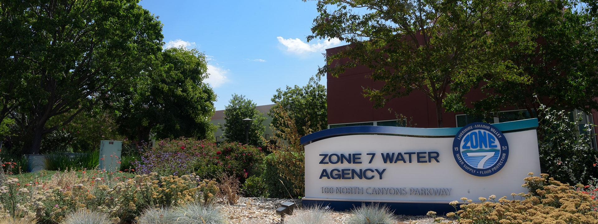 The Zone 7 Water Agency Headquarters monument sign in front of trees and a blue sky in the background