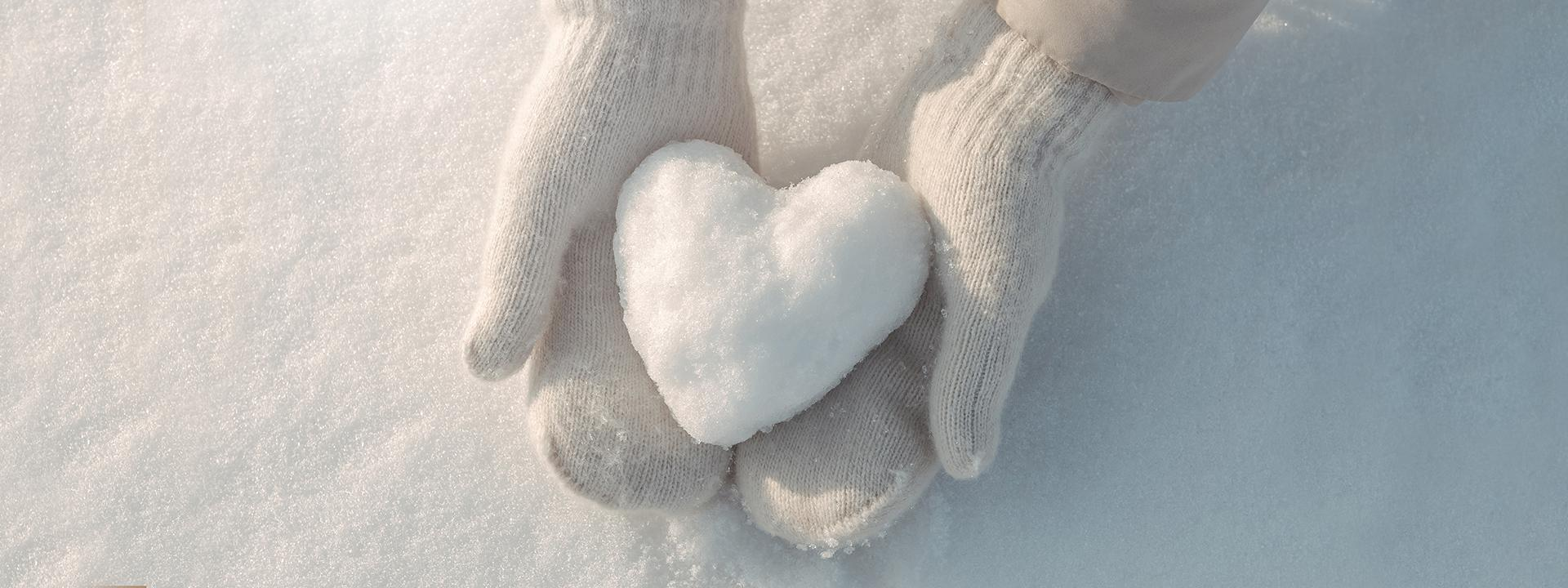 A child wearing white mittens delicately holding a heart-shaped snowball against a snowy background