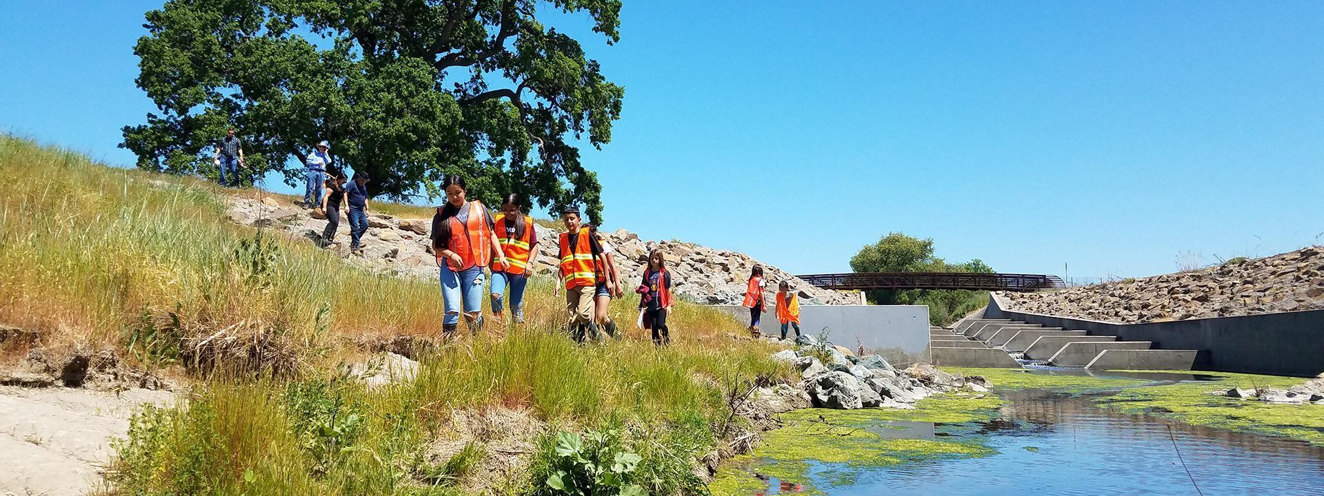Children wearing orange safety vests walking along a creek