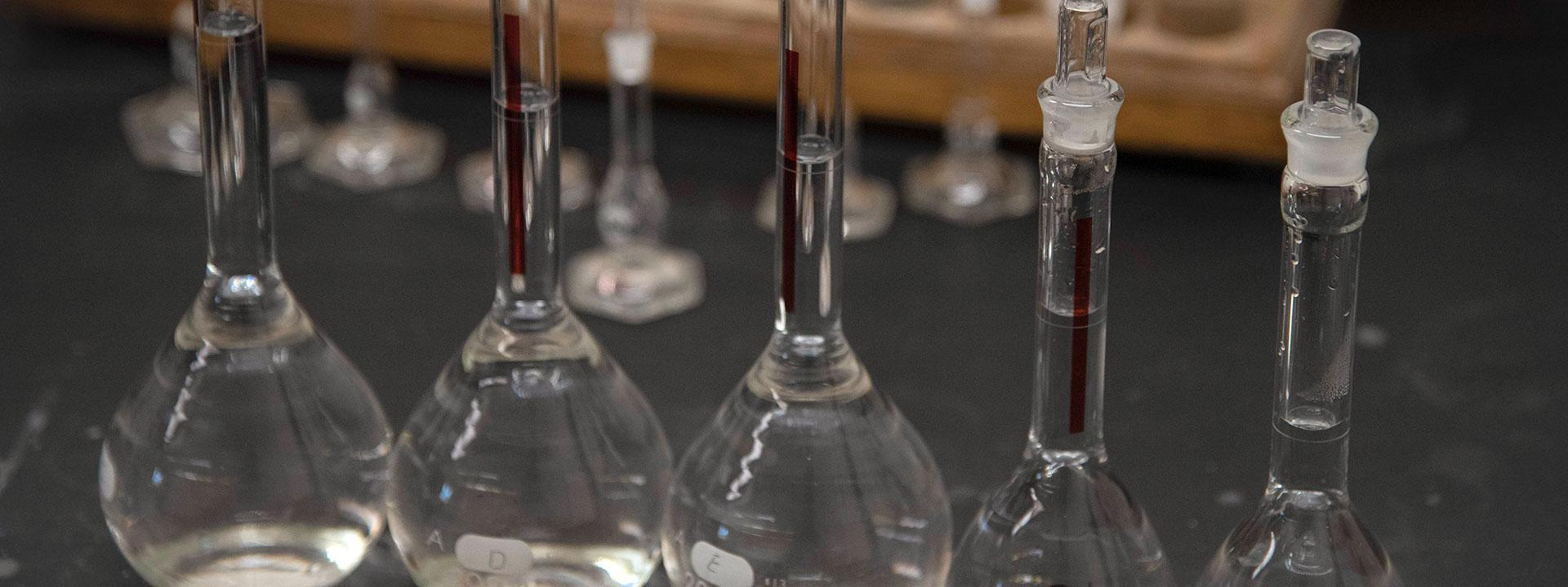 Close up of test tubes and beakers filled with a clear liquid