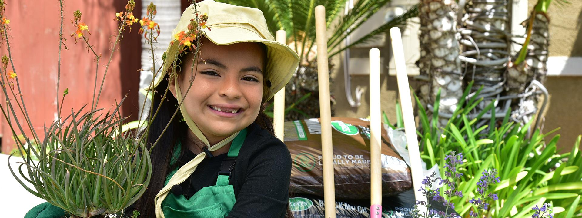 Child smiling wearing sunhat and gloves holding potted plant