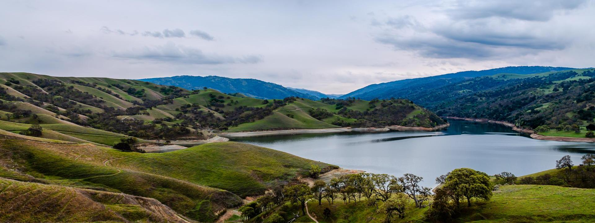 Del Valle Lake surrounded by green hills and gray sky