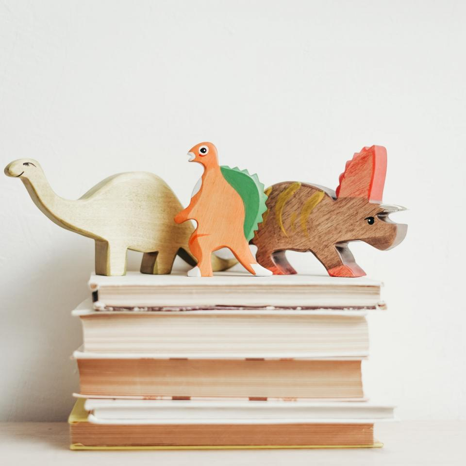 A stack of books with dinosaurs toys sitting on top